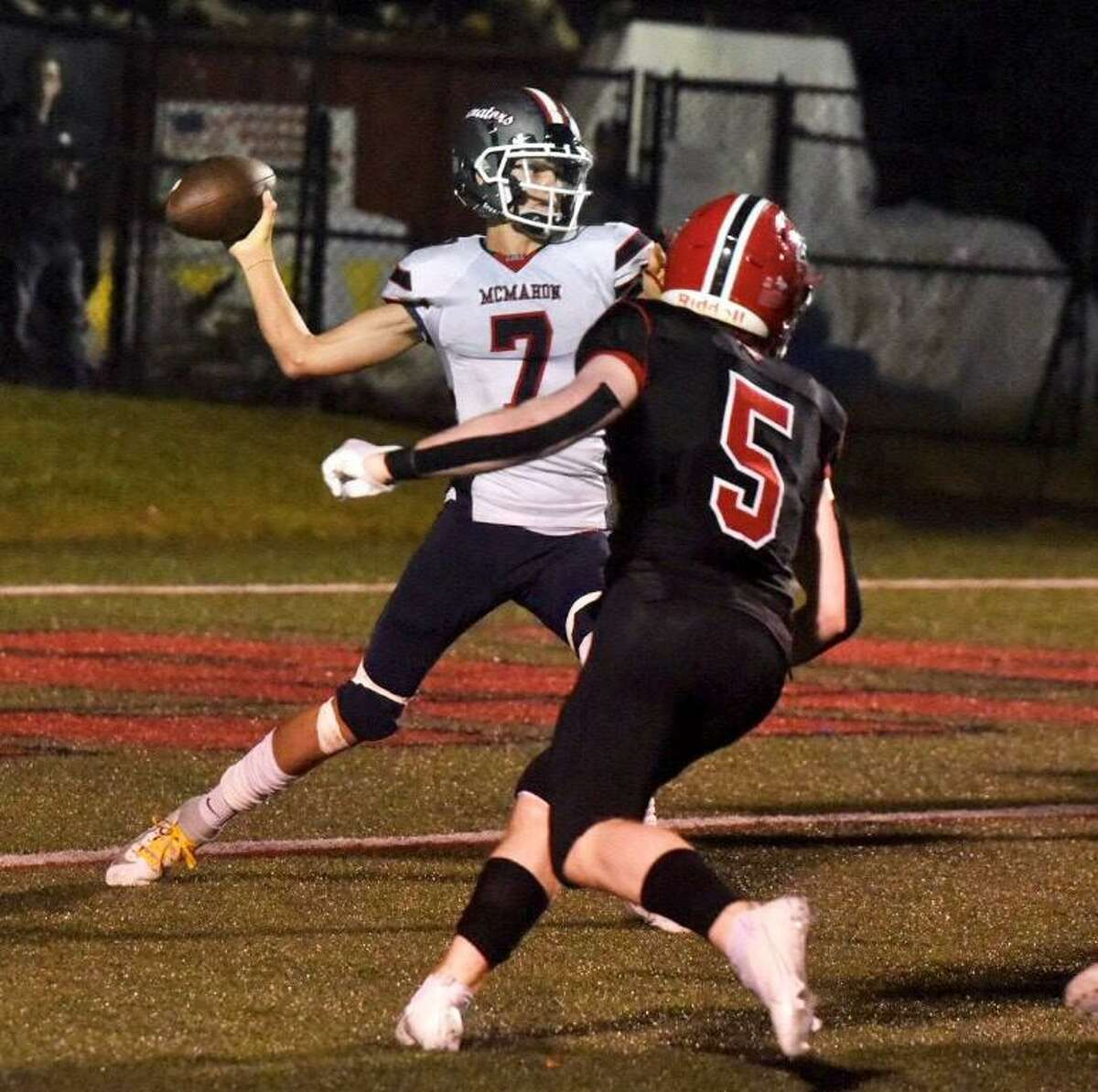 Brien McMahon quarterback Callum Letters (7) passes while pressured by New Canaan's Ryan Werneburg (5) during a football game on Friday, Sept. 17, 2021 at Dunning Stadium in New Canaan, Conn.