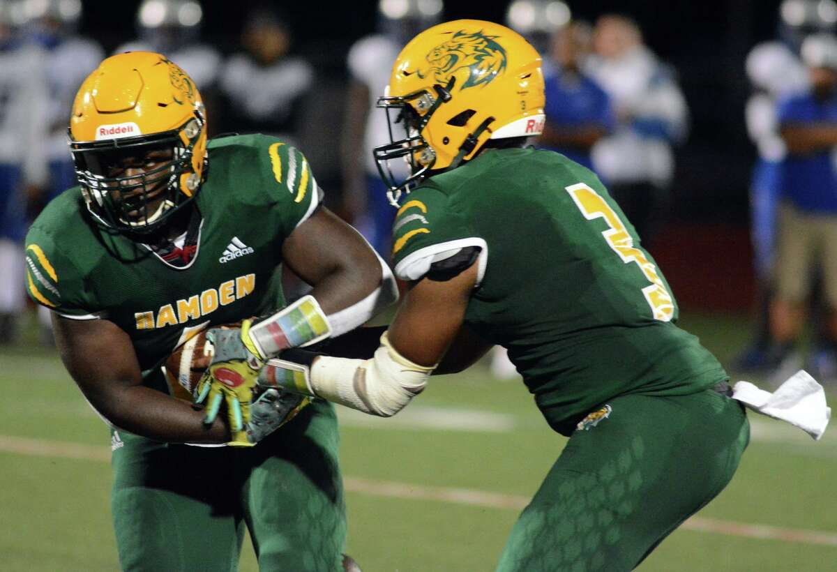 J.J. Gibson Jr. of Hamden hands the football off to Sam Doumah during Friday's game.