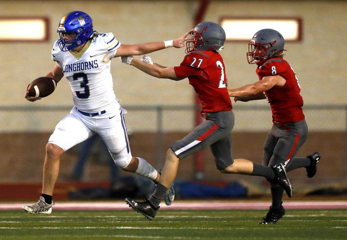 Hampshire-Fannett quarterback Kheagian Heckaman (3) stiff-arms Splendora defensive back Logan Mueller (27) on his way to a 96-yard touchdown as inside linebacker Judson Dean (8) gives chase during the first quarter of a high school football game, Friday, Sept. 16, 2021, in Splendora.