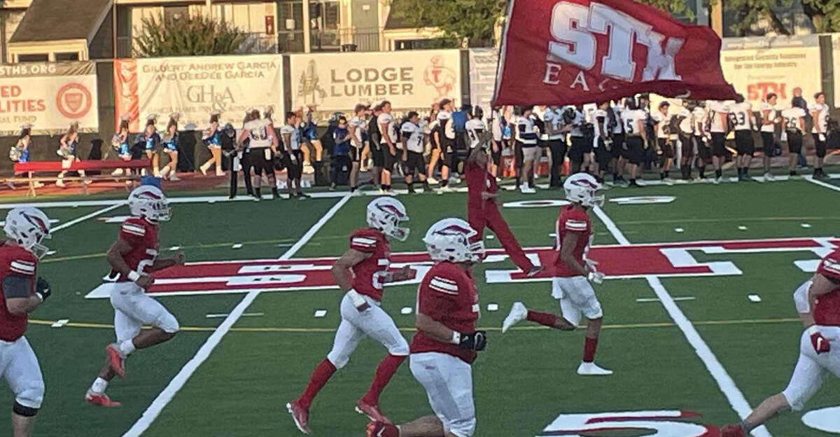 A member of the St. Thomas Eagle Guard waves the school flag as the players run on the field to start the game at St. Thomas' Hotze field at Granger Stadium.