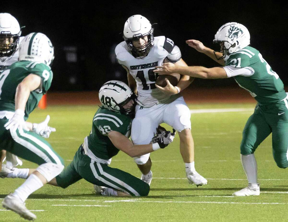 Cistercian quarterback Dan O'Toole (19) is tackled down by Jon Cooper Connor Dove (48) and Owen Baadsgaard (21) during the first quarter of a Southwest Prep 3A football game at The Woodlands Christian Academy, Friday, Sept. 17, 2021, in The Woodlands.