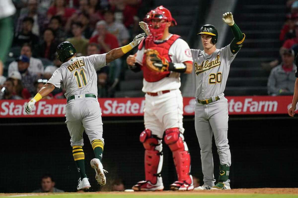 Oakland Athletics designated hitter Khris Davis (11) celebrates with Mark Canha (20) after scoring off of a sacrifice fly hit by Matt Olson during the second inning of a baseball game Friday, Sept. 17, 2021, in Anaheim, Calif. Los Angeles Angels catcher Kurt Suzuki, center, reacts. (AP Photo/Ashley Landis)