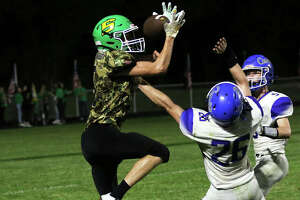 Southwestern's Collin Robinson catches a 19-yard touchdown pass behind Greenville defenders Davin Johnson (26) and Landen Moss (right) in the final seconds of the first half Friday night at Knapp Field in Piasa.