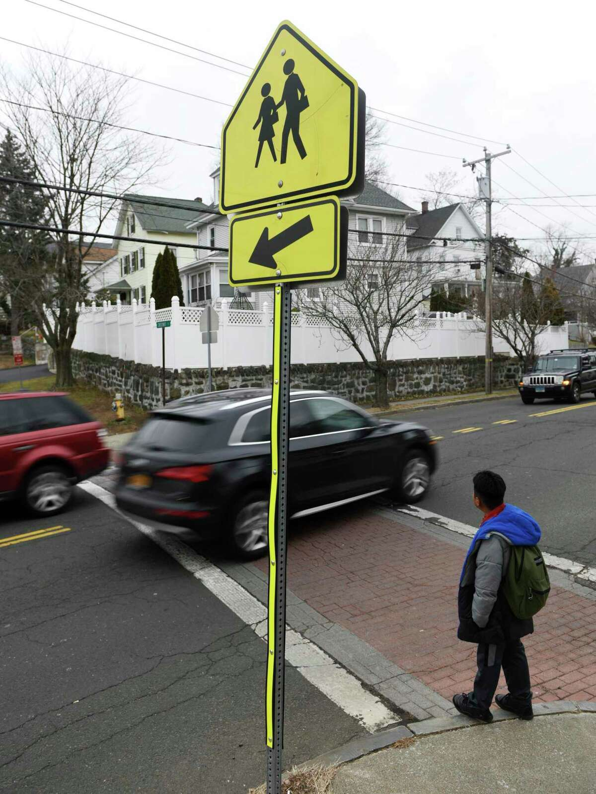 A student waits to cross the street after dismissal from New Lebanon School as cars speed by without stopping at the crosswalk at the intersection of Delavan Avenue and New Lebanon Avenue in the Byram section of Greenwich, Conn. Tuesday, Jan. 14, 2020.