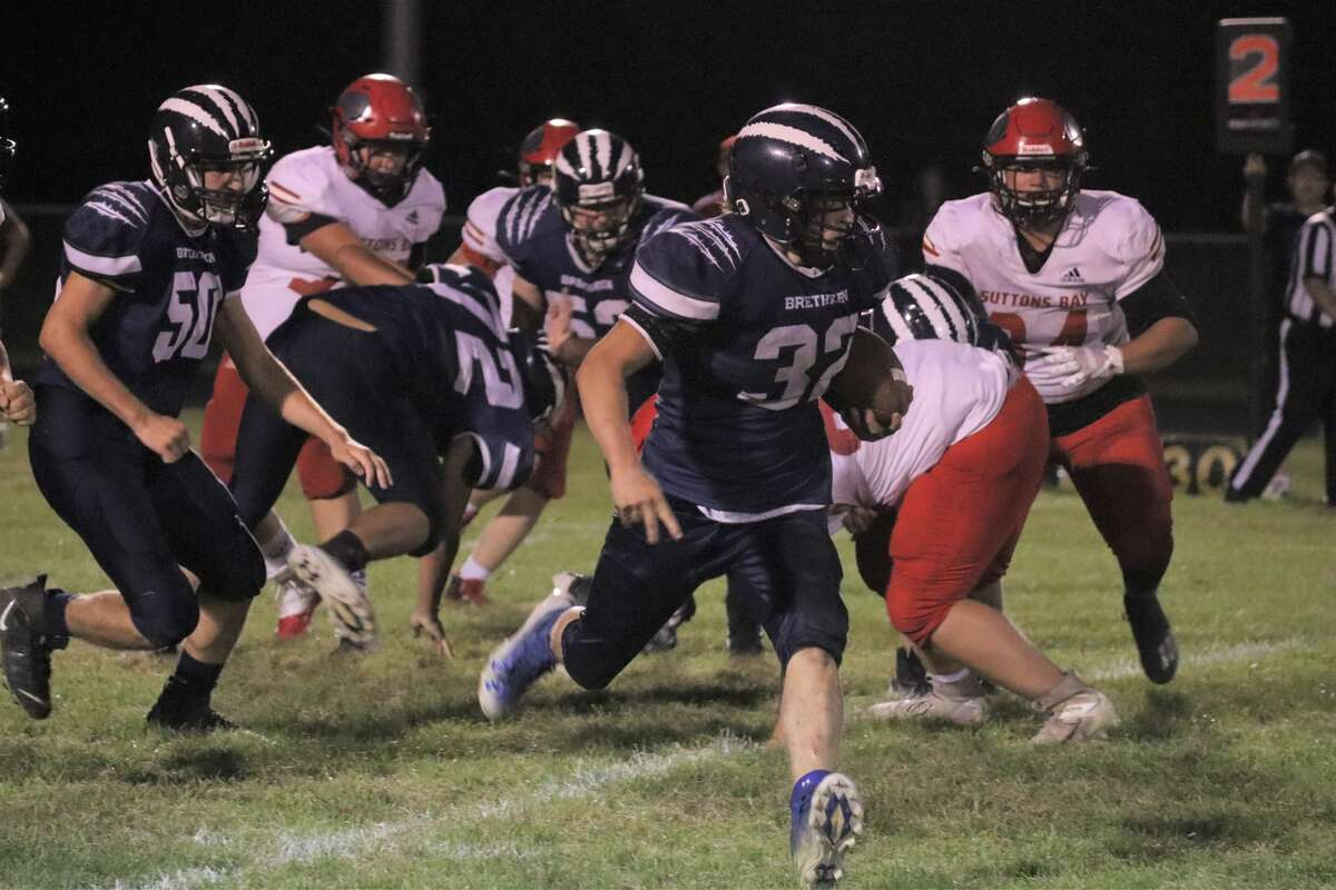 Zander Bowers bursts through an opening on his way to a 78-yard rushing performance against Suttons Bay on Sept. 17.