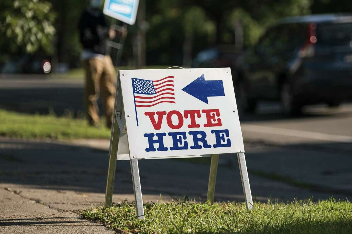 """A """"Vote Here"""" sign is displayed outside a polling location in Minneapolis on Aug. 11, 2020."""