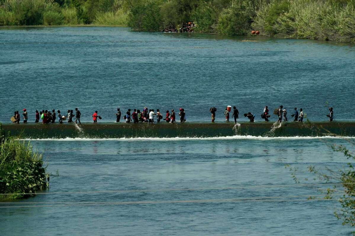 Haitian migrants use a dam to cross to and from the United States from Mexico, Friday, Sept. 17, 2021, in Del Rio, Texas. Thousands of Haitian migrants have assembled under and around a bridge in Del Rio presenting the Biden administration with a fresh and immediate challenge as it tries to manage large numbers of asylum-seekers who have been reaching U.S. soil.