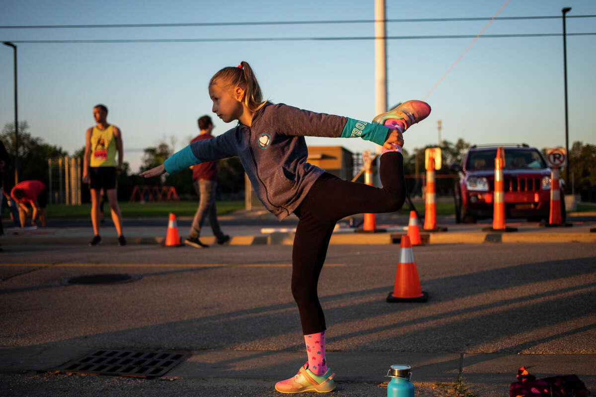 Alexis Luft of Midland, 11, stretches before participating in a 5K run during the 2021 Dow RunWalk Saturday, Sept. 18, 2021 in Midland. (Katy Kildee/kkildee@mdn.net)