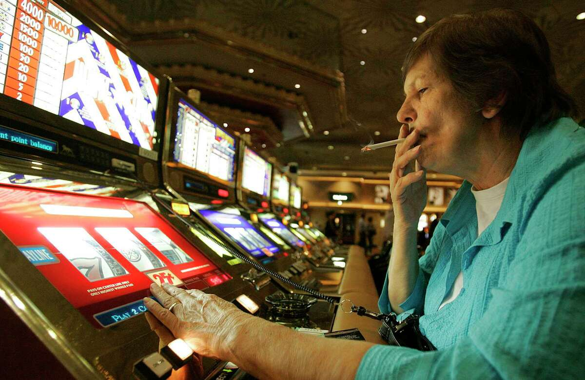 In this Dec. 28, 2005, photo, Judy King of Daytona Beach, Fla., holds a cigarette while playing a slot machine at the MGM Grand hotel and casino in Las Vegas.