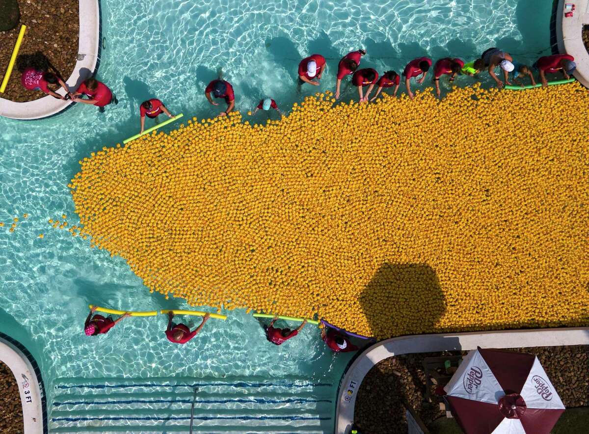 Volunteers guide rubber ducks down the lazy river at Big Rivers Waterpark during Community Assistance Center's duck race, Saturday, Sept. 18, 2021, in New Caney. The annual event raises money for the non-profit that provides resources and needs to struggling individuals and families in Montgomery County.