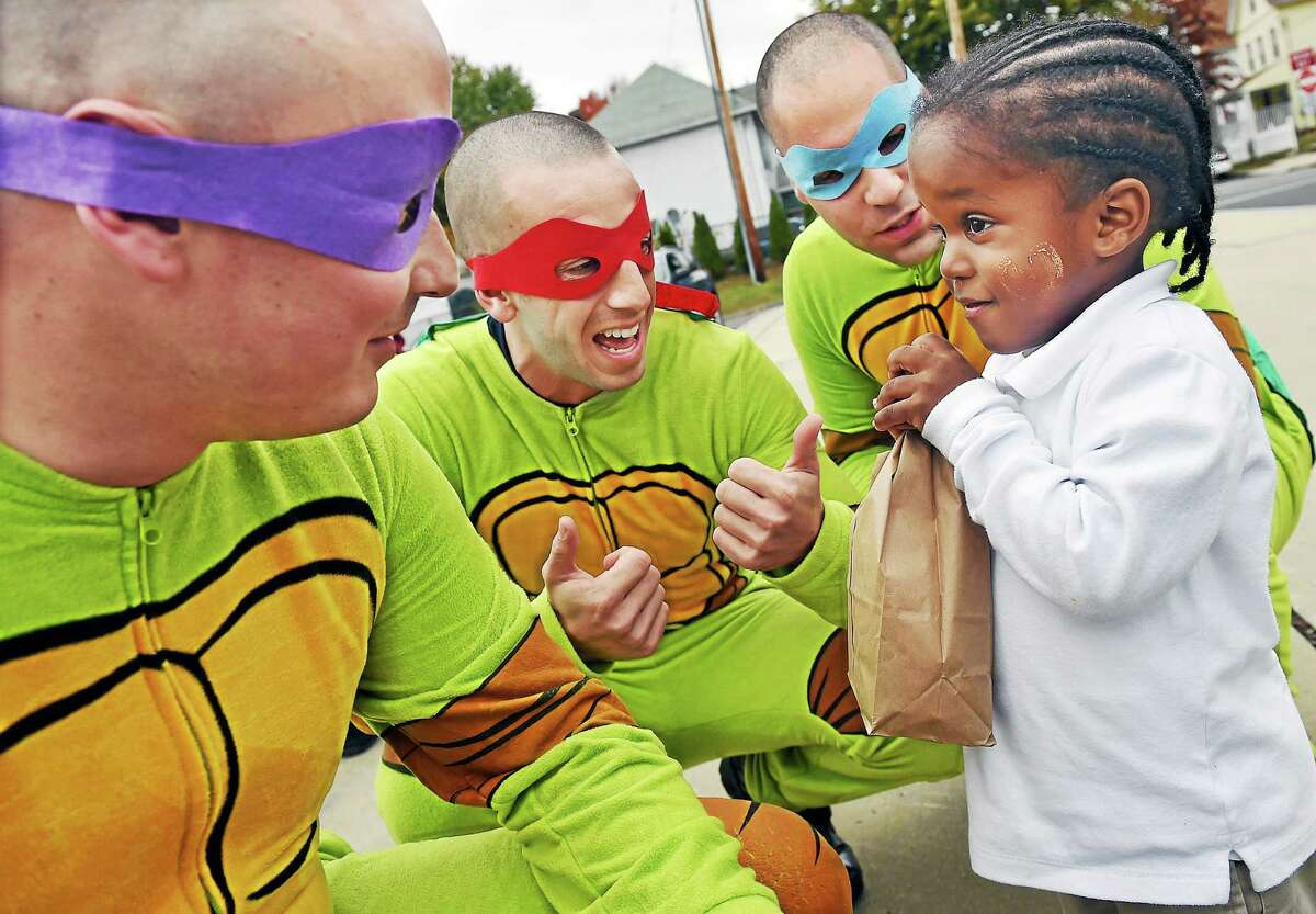 """(Catherine Avalone - New Haven Register) ¬ Pre-k student Trevon Williams, 3, clutches his bag of candy while discussing his Halloween costume with the """"Ninja Turtle"""" police recruits Timothy Janus, Joshua Castellano and Joesph Perrotti, left toright, at the Trunk or Treat sponsored by the New Haven Police Academy at the King/Robinson Inter-District Magnet School on Friday afternoon, October 31, 2014."""