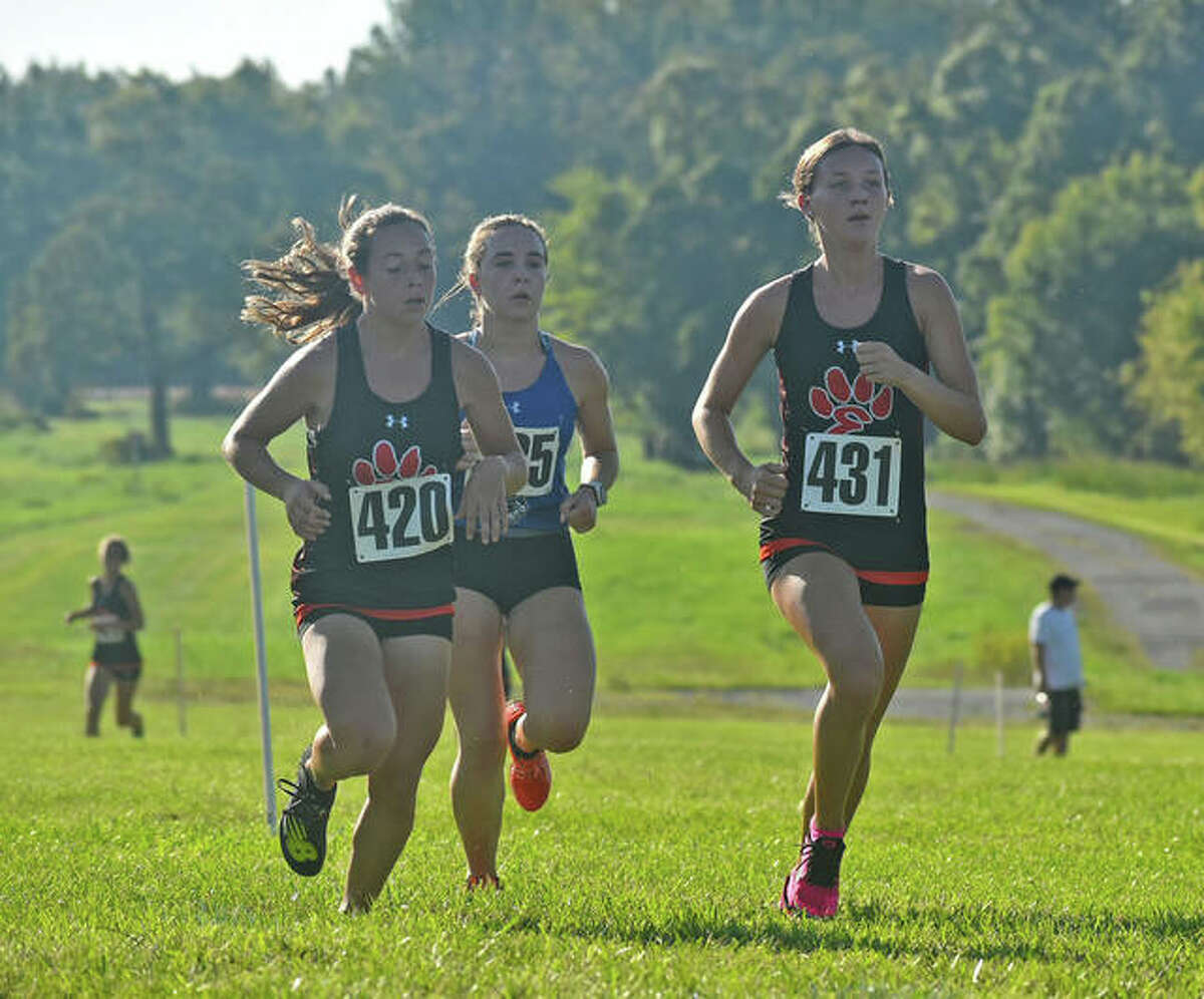 Edwardsville's Emily Nuttall, right, and Olivia Coll, left, lead the pack one mile into the Edwardsville Invitational on Saturday at SIUE.