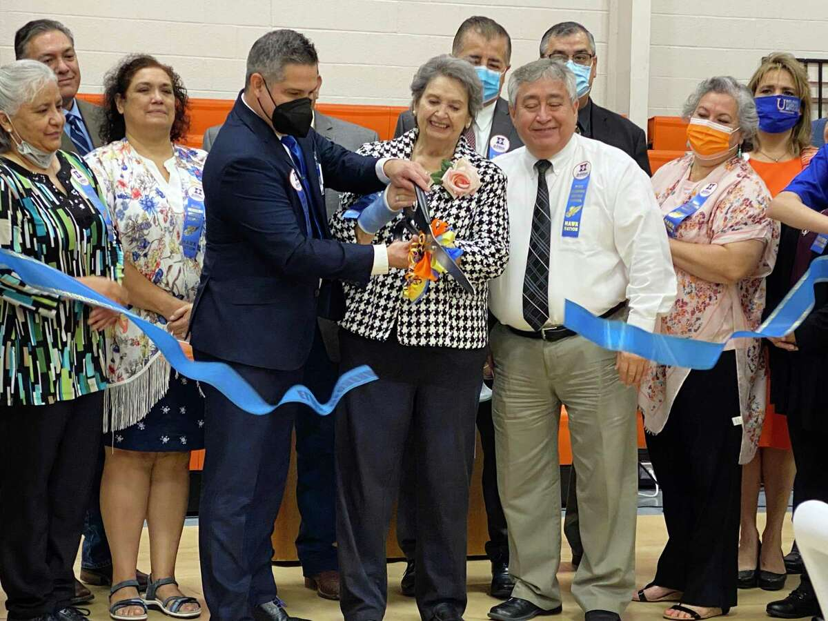 Olga Herrera and Principal Carlos Martinez cut the ribbon in honor of Elias Herrera Middle School and the legacy set 60 years prior at the EHMS gym on Friday Sept. 17, 2021.