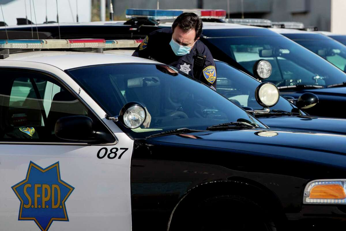 A police officer enters his patrol vehicle outside of the Bayview Police Station in San Francisco, Calif.