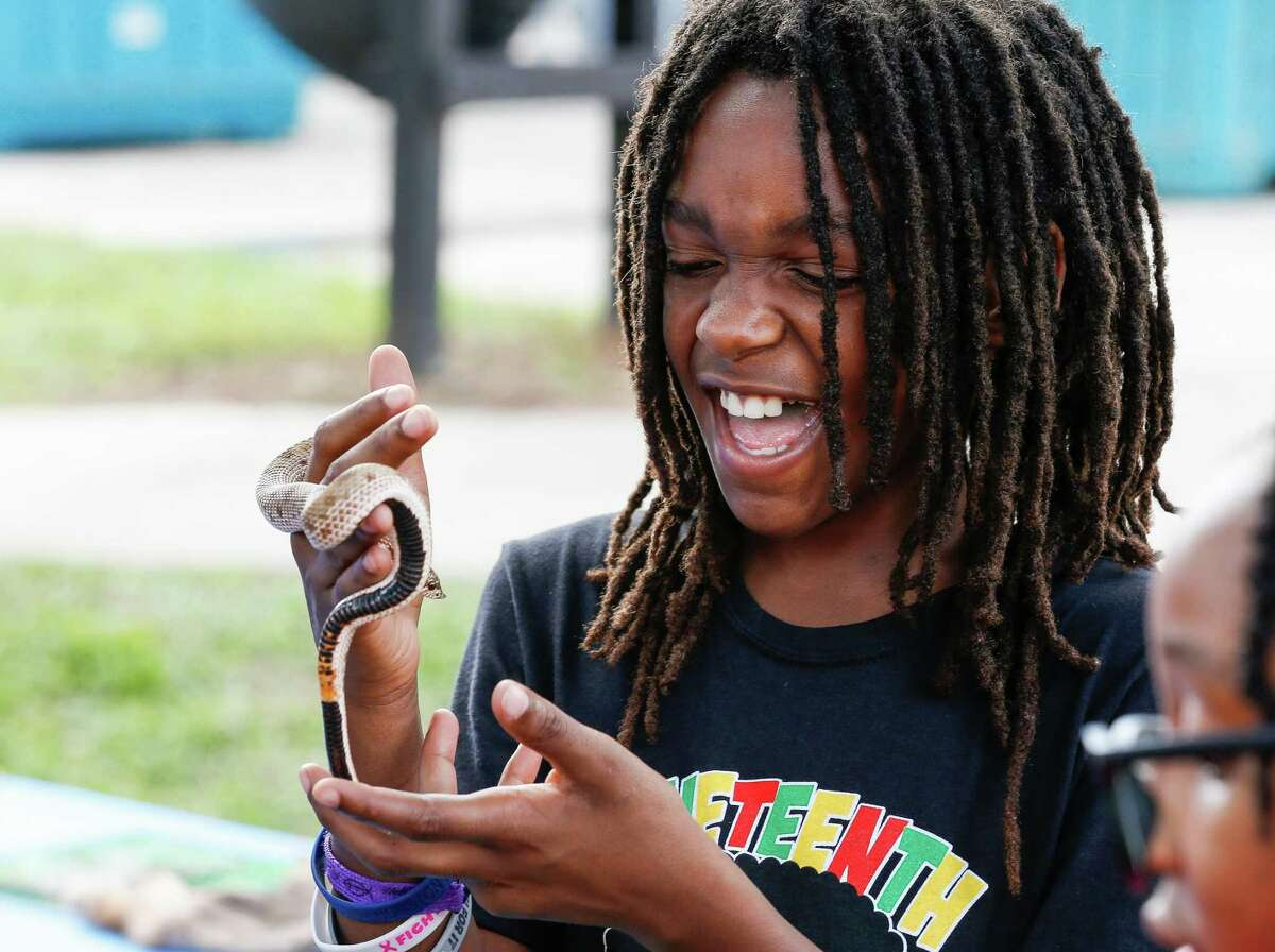 Micah Nubin, 10, reacts to holding a snake during the Love Our Parks Fest at Our Park on Saturday, Sept. 18, 2021, in Third Ward.