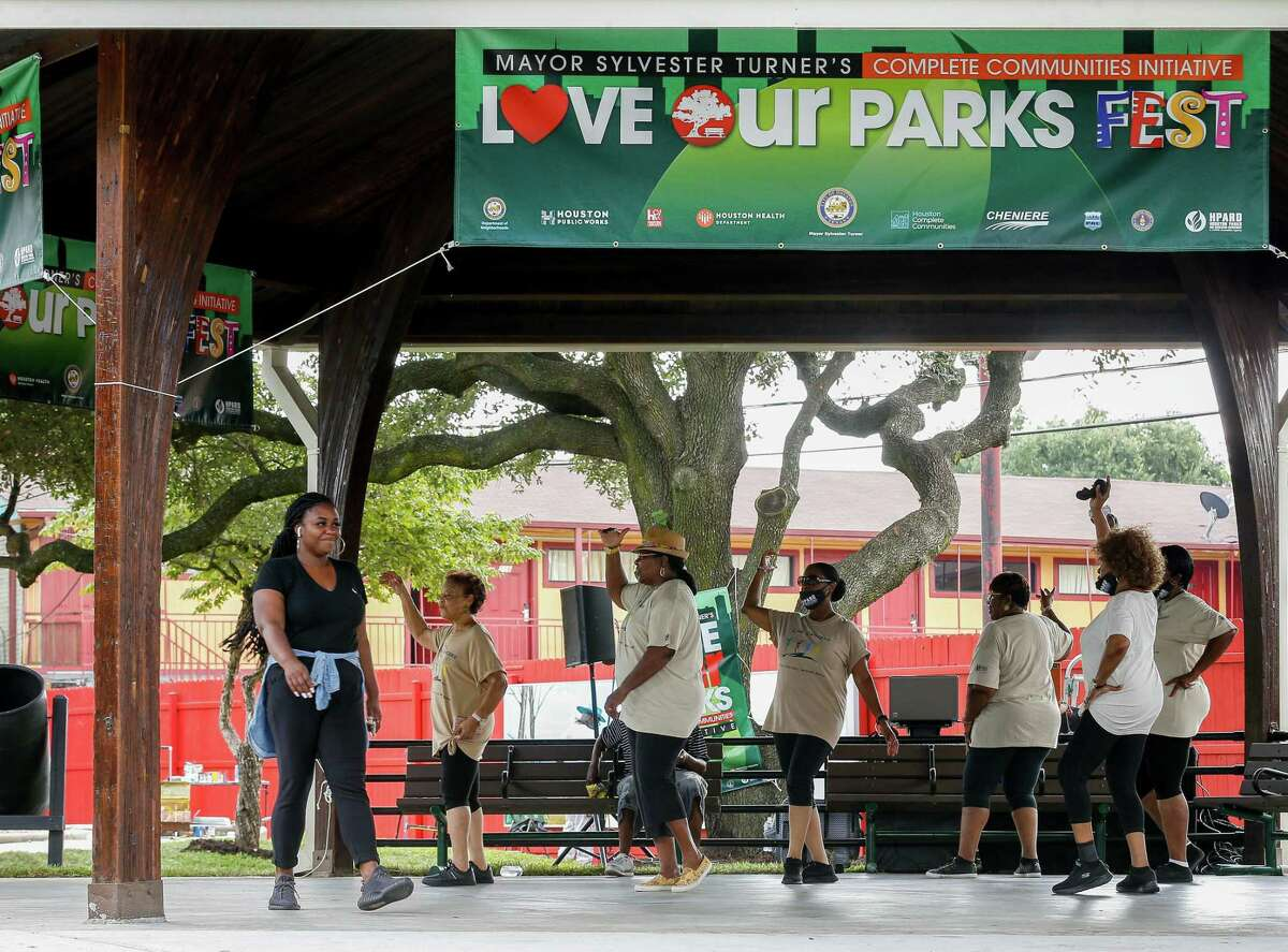 A group of women line dance to the rhythm of music playing at Our Park, during the Love Our Parks Fest on Saturday, Sept. 18, 2021, in Third Ward.