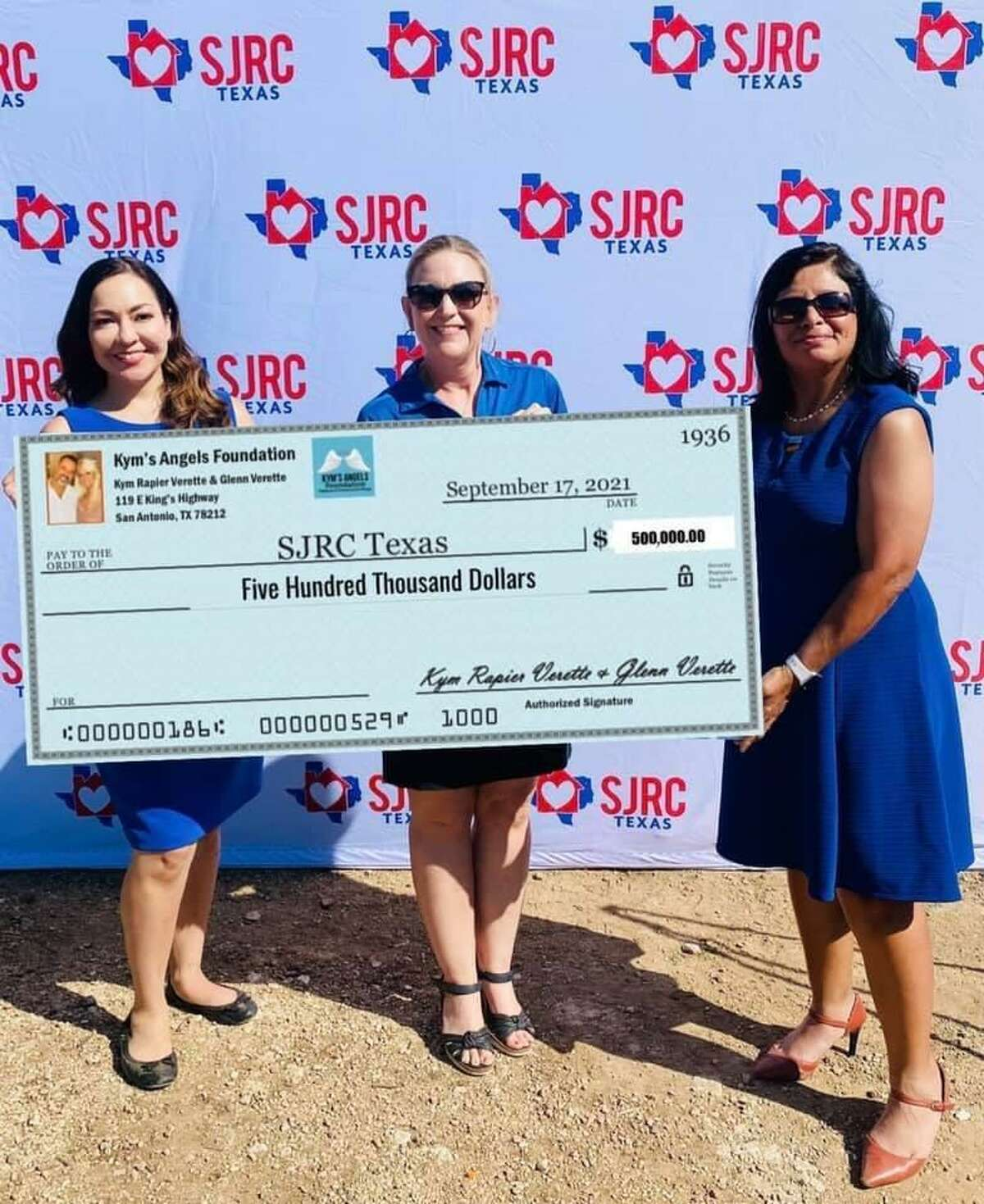 SJRC Texas Chief Development Officer Cynthia Lopez, from left, SJRC CEO Tara Roussett and a spokesperson for the Verettes, Yolanda Valenzuela, display a giant check marking the Verettes' $500,000 donation.