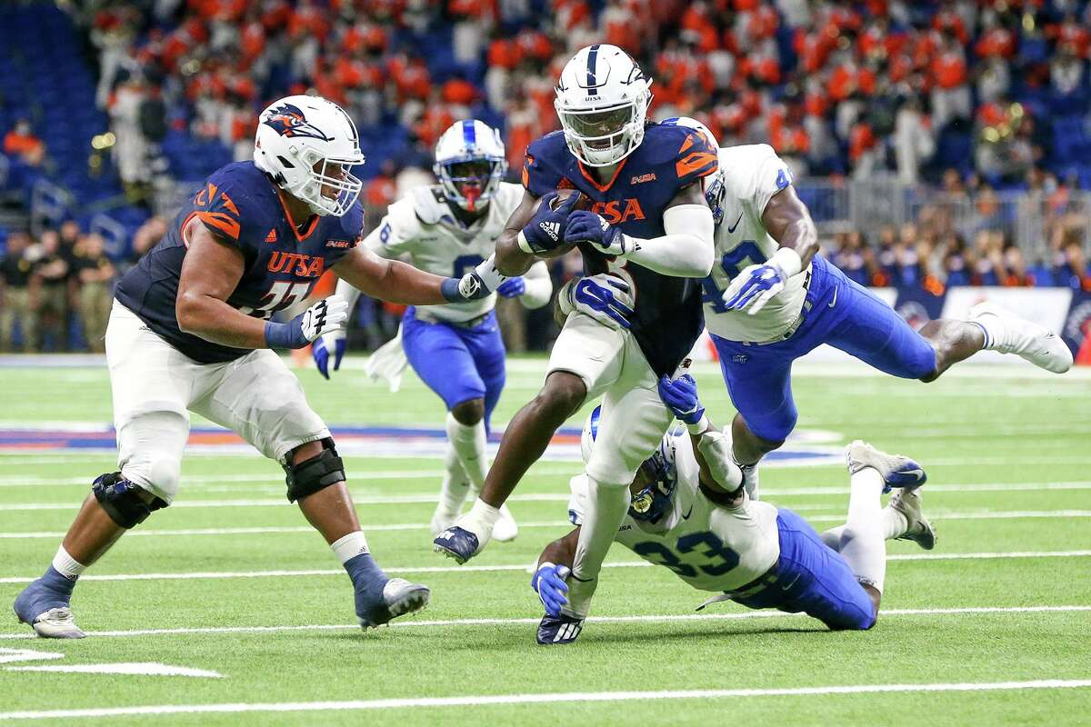 UTSA running back Sincere McCormick tries to escape from Middle Tennessee's Decorian Patterson, below and Jorden Starling during the first half of their opening Conference USA football game at the Alamodome on Saturday, Sept. 18, 2021.