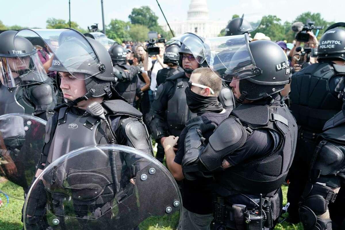 Varios policías rodean a un hombre (al centro, con anteojos) durante un mitin cerca del Capitolio de Estados Unidos el sábado 18 de septiembre de 2021, en Washington, D.C.