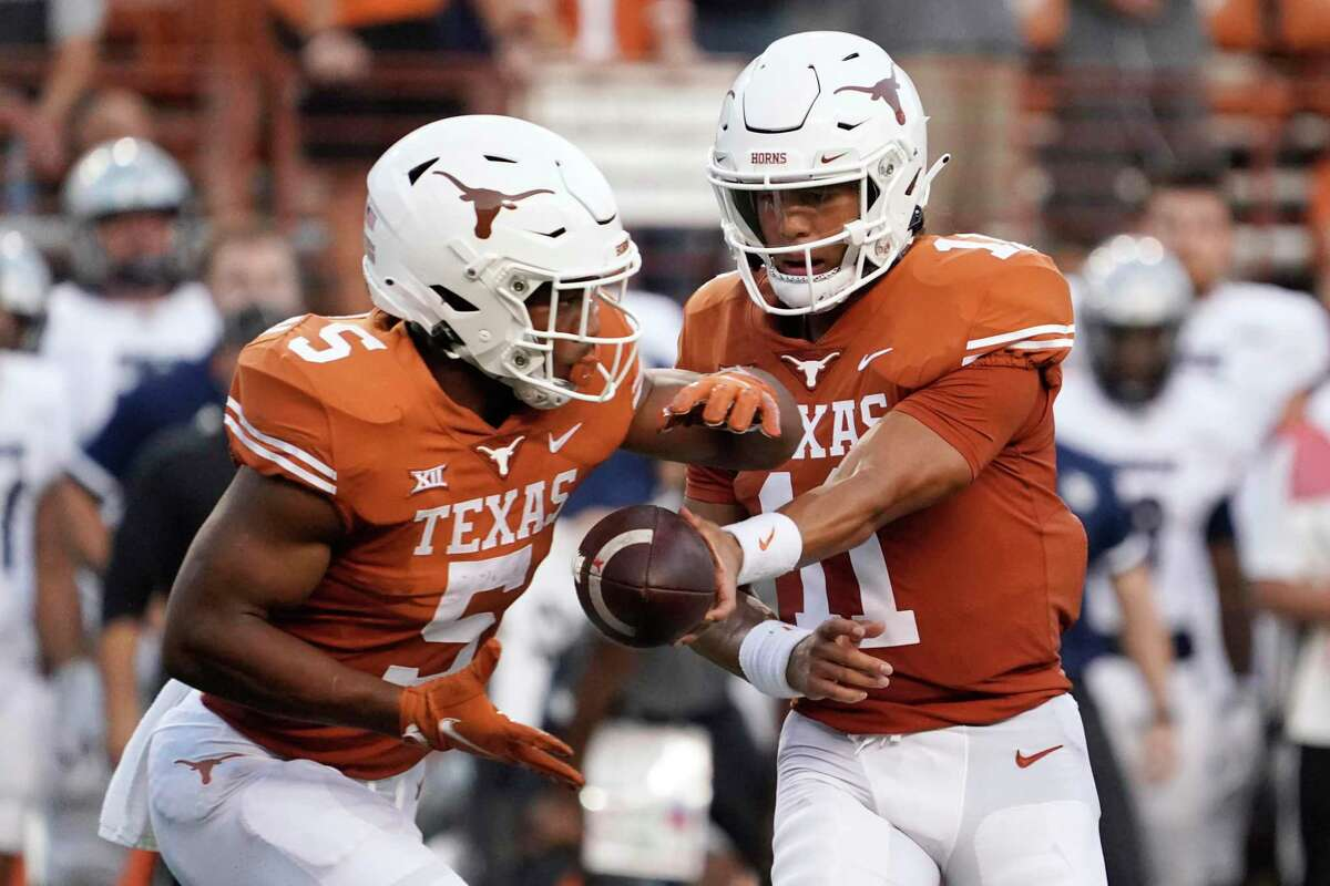 Texas quarterback Casey Thompson (11) hands the ball off to Bijan Robinson (5) during the first half of the team's NCAA college football game against Rice on Saturday, Sept. 18, 2021, in Austin, Texas. (AP Photo/Chuck Burton)