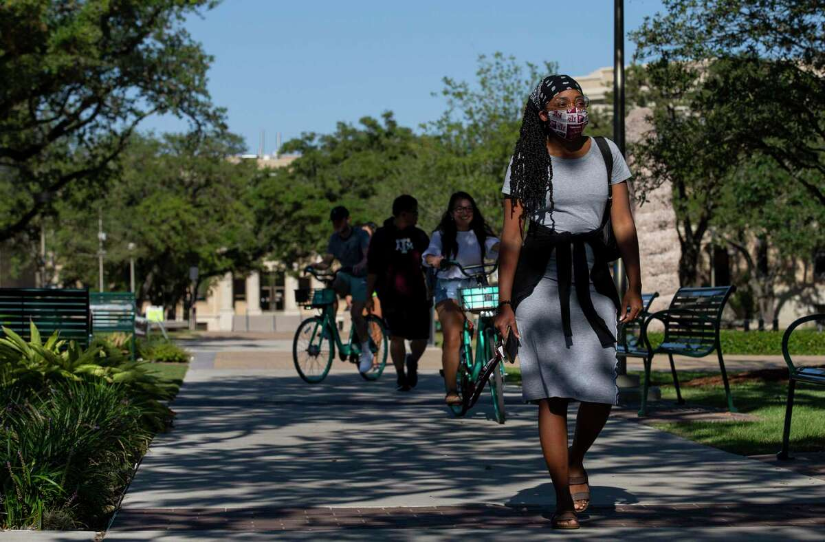Texas A&M students wear masks on campus in College Station. The death of a 20-year-old Texas A&M University student from COVID-19 has spurred some students and faculty members to demand more stringent coronavirus precautions.