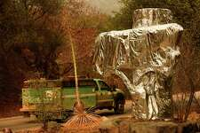 A US Forest Service vehicle drives past the Sequoia National Park historic park entrance sign wrapped in fire resistant foil along Generals Highway during a media tour of the KNP Complex fire in the Sequoia National Park near Three Rivers, California on September 18, 2021.