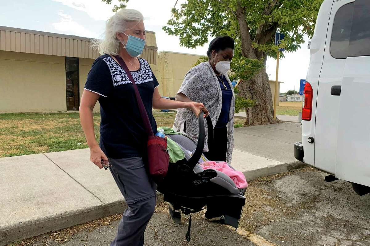 Aid worker, Tiffany Burrow, left, and Guerline Jozef, with the Haitian Bridge Alliance, hold six-day-old Grace Francesca Xavier outside the Val Verde Humanitarian Border Coalition in Del Rio, Texas on Saturday, Sept. 18th, 2021, as her parents board a bus to San Antonio. Grace was delivered by C-Section after her mother says she went into labor near the border crossing. The baby's parents fled Haiti two months ago.