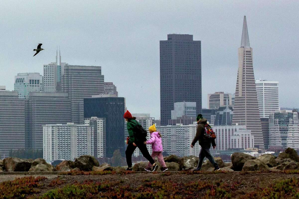 Drizzling rain falls as a group of people begin to walk faster down the path at Treasure Island, Friday, Nov. 13, 2020, in San Francisco, Calif.