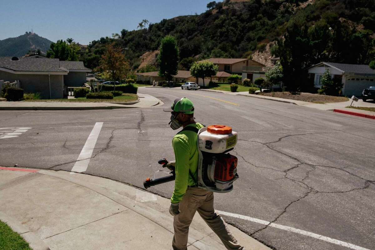 A representative of the company Mosquito Squad performs a house call in the Glendale, Calif., area on Sept. 13, 2021. The company, which douses yards with pest control agents, has opened new franchises in Southern California.