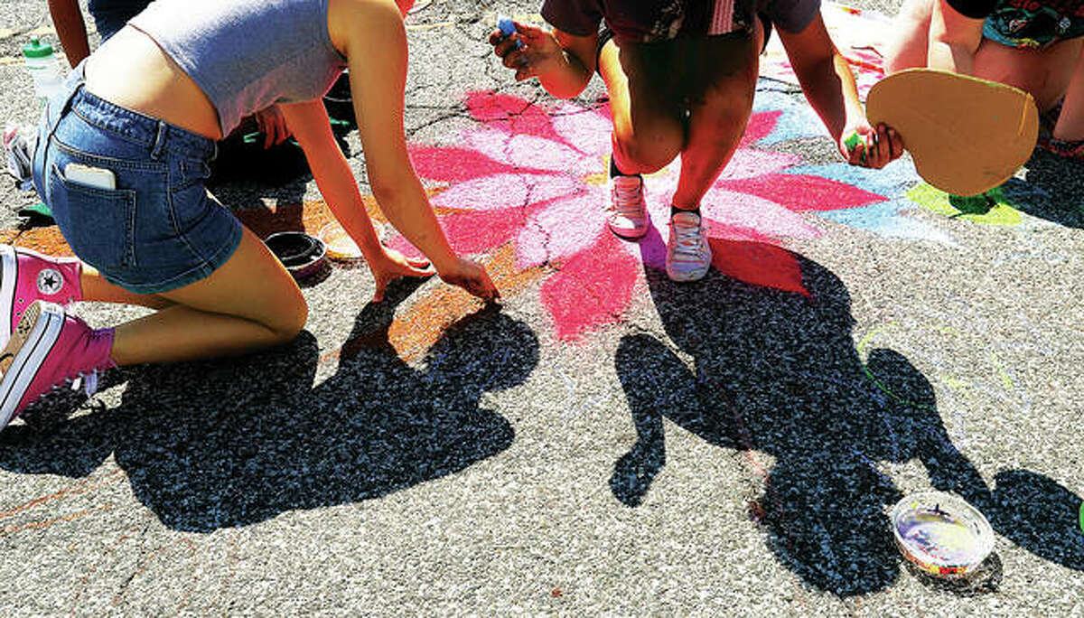 The sun casts the shadow of two people doing chalk drawings in the street during the 15th annual Mississippi Earthtones Festival in Alton on Saturday.