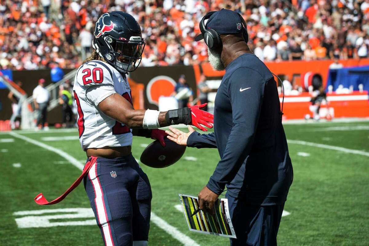 Houston Texans safety Justin Reid (20) is met at the sidelines by defensive coordinator Lovie Smith after Reid intercepted a pass by Cleveland Browns quarterback Baker Mayfield during the first half of an NFL football game Sunday, Sept. 19, 2021, in Cleveland.