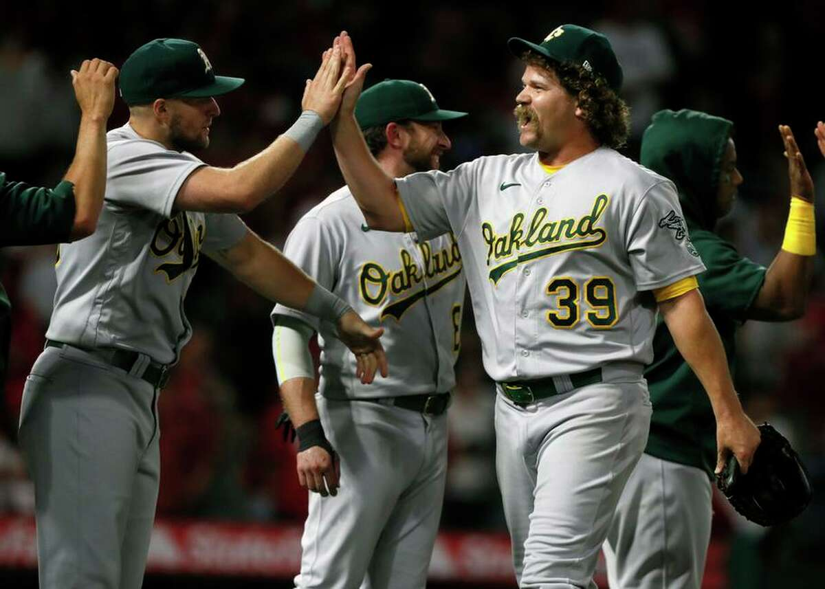 Oakland Athletics relief pitcher Andrew Chafin celebrates with teammates after a baseball game against the Los Angeles Angels in Anaheim, Calif., Saturday, Sept. 18, 2021. (AP Photo/Alex Gallardo)