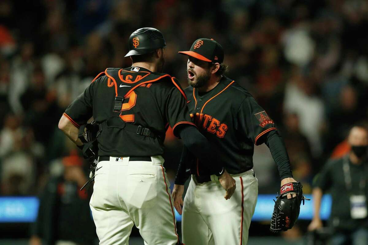 SAN FRANCISCO, CALIFORNIA - SEPTEMBER 18: Catcher Curt Casali #2 and closing pitcher Dominic Leone #52 of the San Francisco Giants celebrate after a win against the Atlanta Braves at Oracle Park on September 18, 2021 in San Francisco, California. (Photo by Lachlan Cunningham/Getty Images)
