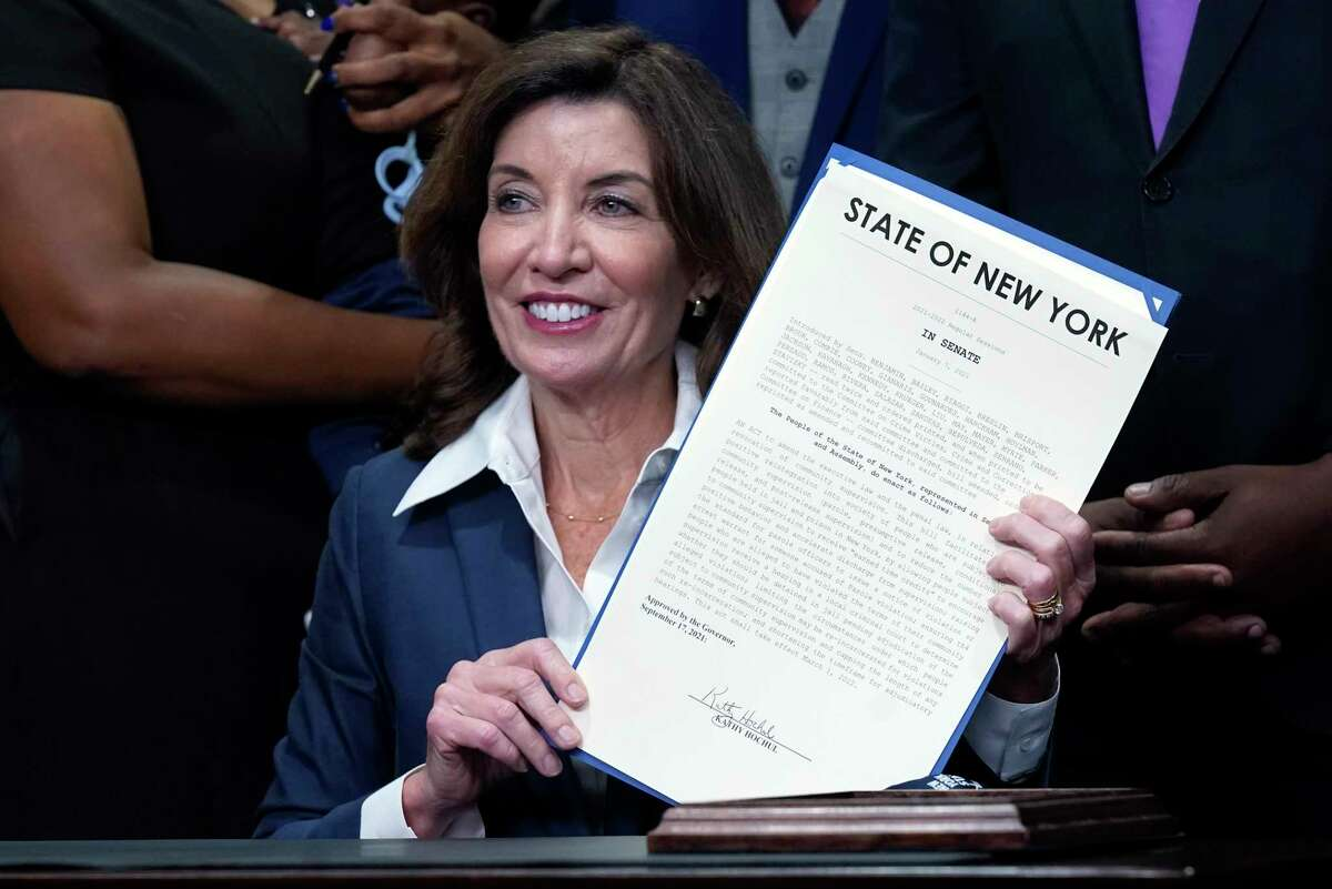 """New York Gov. Kathy Hochul holds the """"Less is More"""" law she signed, during ceremonies in the her office, in New York, Friday, Sept. 17, 2021. Hochul gave the commencement speech at Syracuse University Sunday, Sept. 19, 2021. She graduated from SU in 1980. (AP Photo/Richard Drew)"""