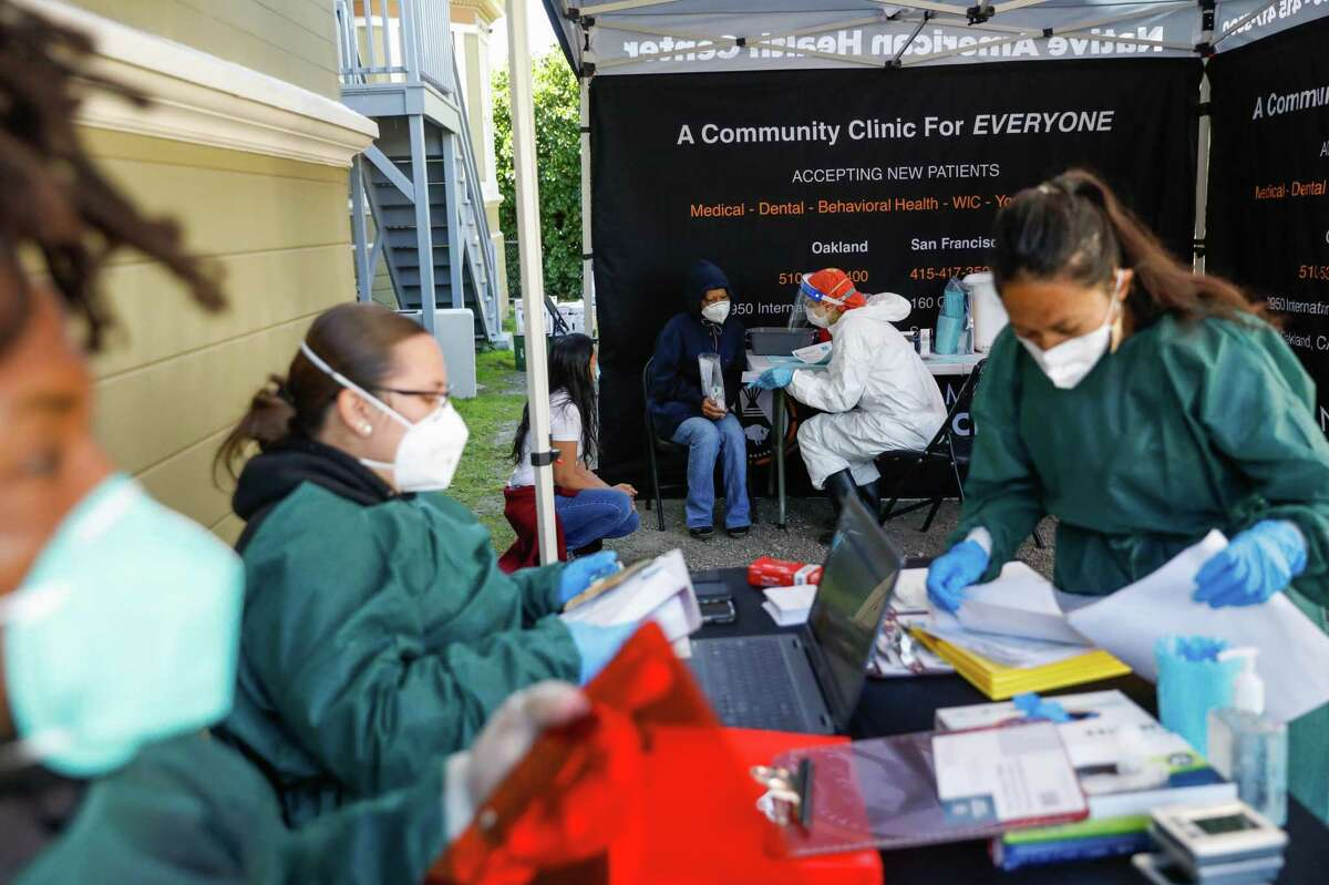 Nurse Anna Briggs (center right) chats with a patient with before administering the Johnson & Johnson COVID-19 vaccine at the Center for Empowering Refugees in collaboration with Native American Health on Friday, March 26, 2021 in Oakland, California.