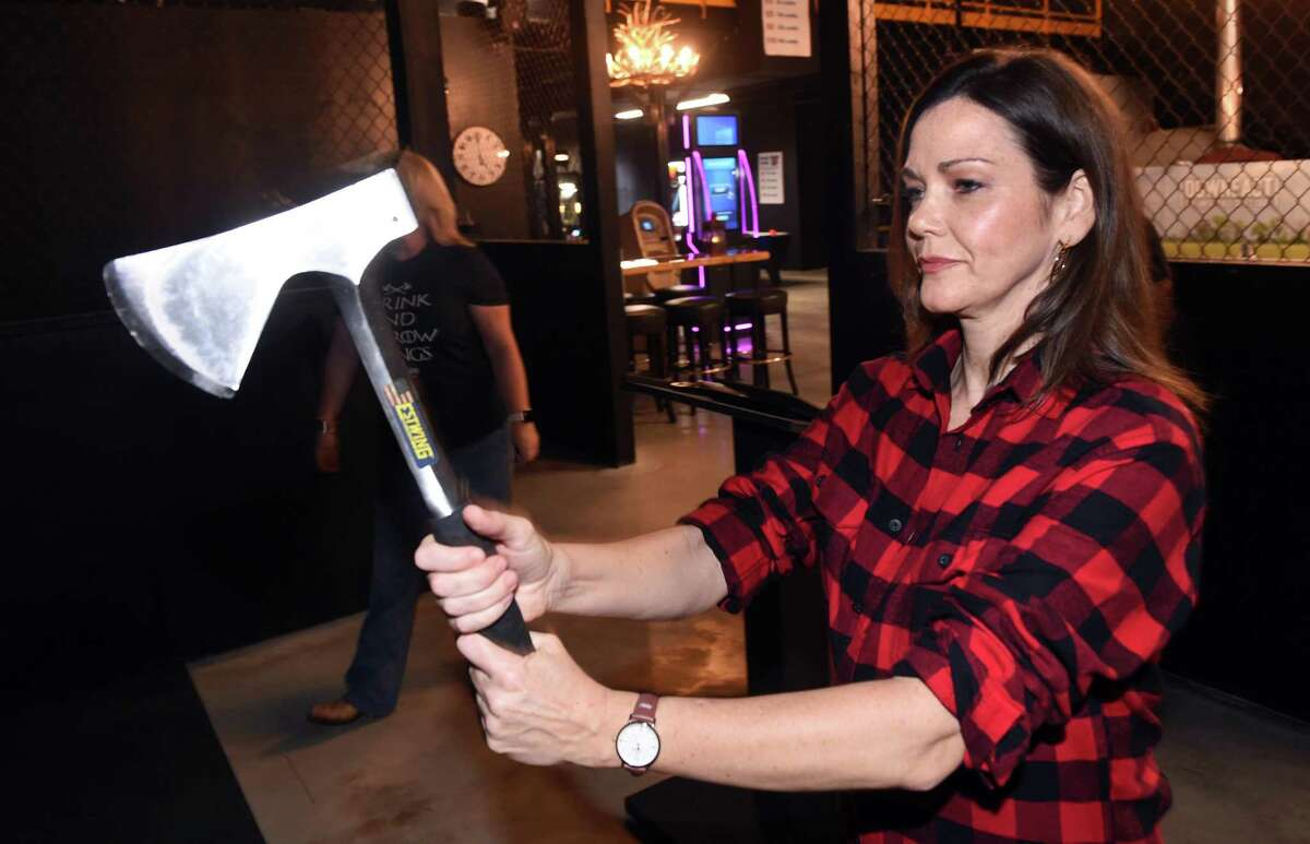 Amy Higgins of Key West, Florida, tries out ax throwing with her sister, Cara (background) at Montana Nights Axe Throwing in Orange on September 17, 2021. Besides ax throwing, the establishment offers a bar, pizza, darts and pool tables.