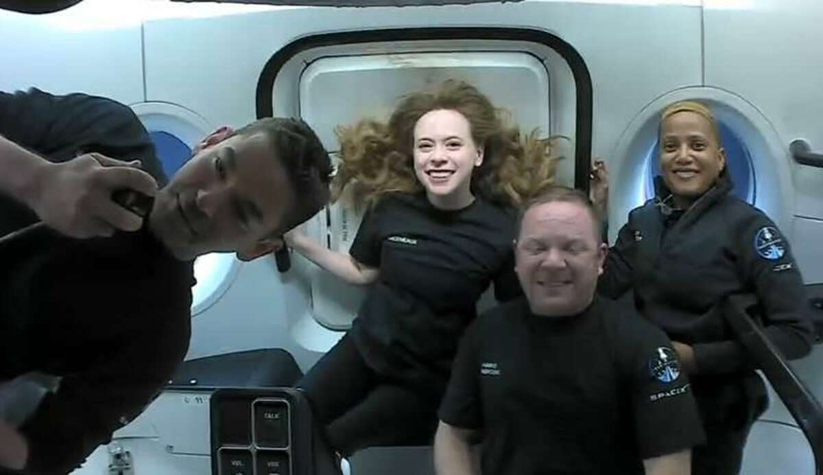 The Inspiration4 crew is shown in the SpaceX Crew Dragon spacecraft while orbiting the Earth. From left is Jared Isaacman, Hayley Arceneaux, Chris Sembroski and Sian Proctor.
