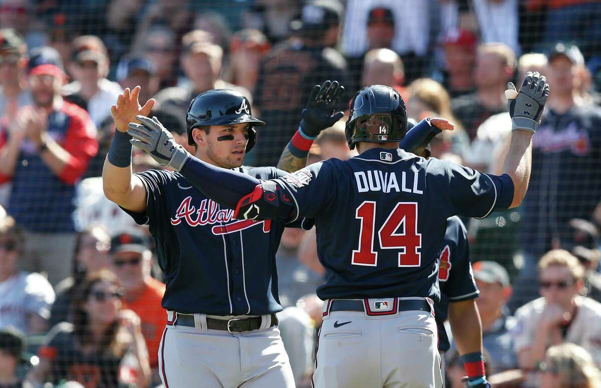 Adam Duvall (14) is greeted at home by Atlanta teammate Austin Riley after his two-run homer off Anthony DeSclafani gave the Braves a 2-0 lead in the seventh inning.