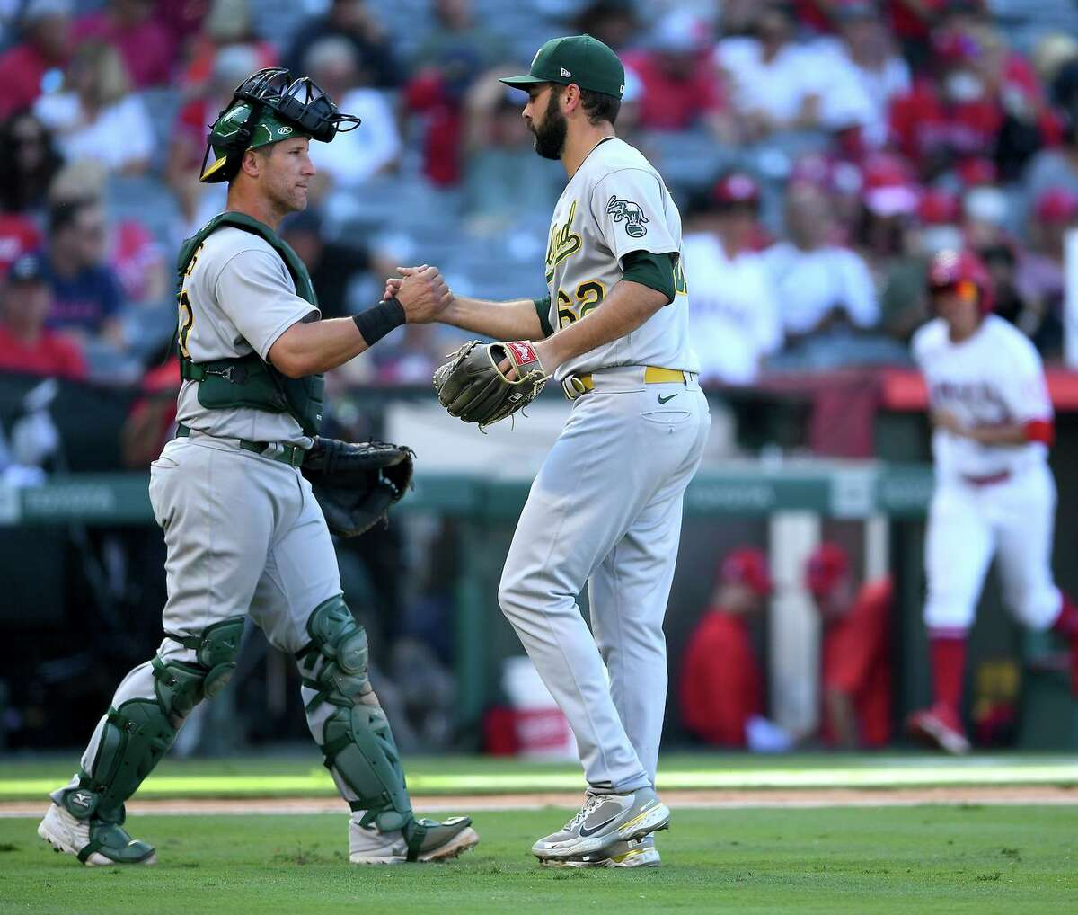 Catcher Yan Gomes (left) celebrates with Lou Trivino, who entered the game in the bottom of the ninth inning before finishing it off in the 10th to be credited with the win.