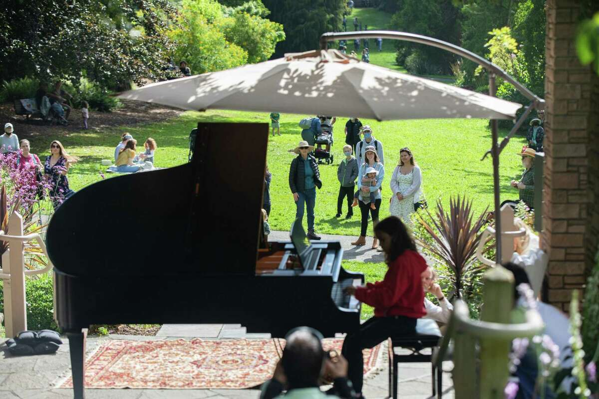 Onlookers in the San Francisco Botanical Gardens in Golden Gate Park enjoy the music of a young pianist during the Flower Piano event.
