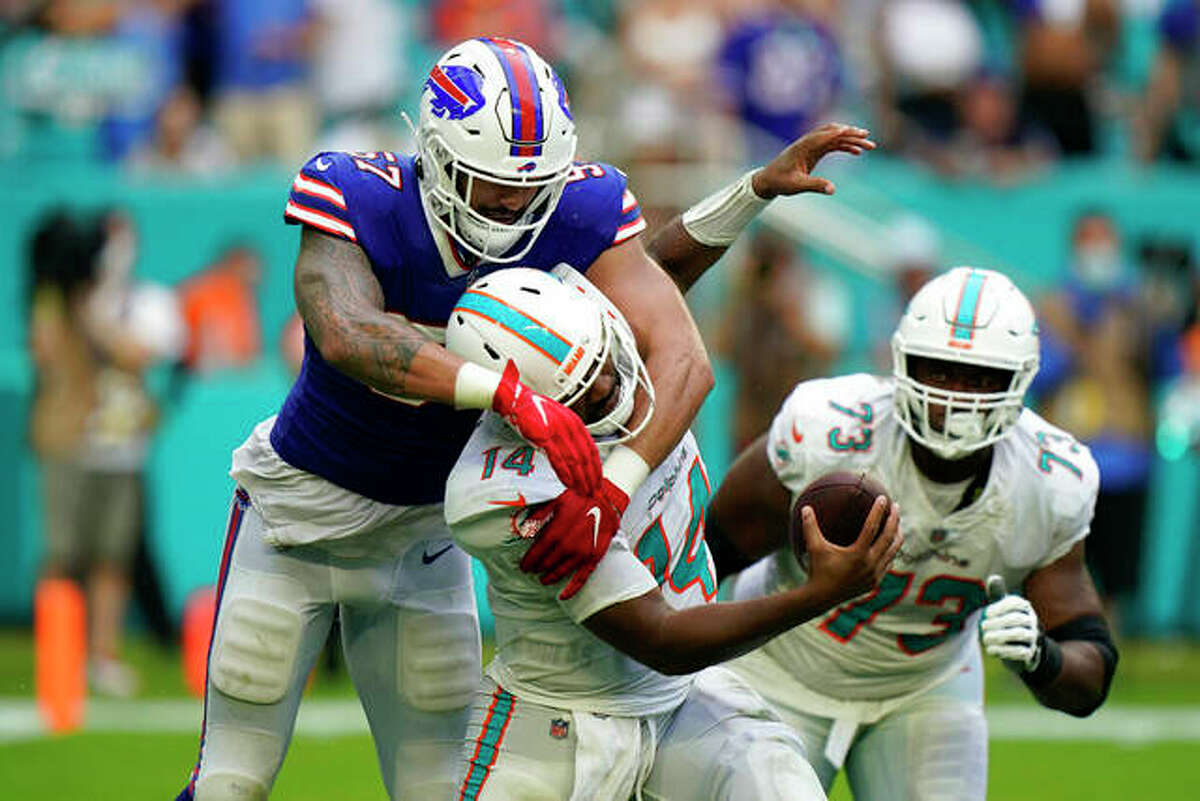Miami Dolphins quarterback Jacoby Brissett (14) is hit by Buffalo Bills defensive end A.J. Epenesa (57) during the second half of an NFL football game, Sunday, Sept. 19, 2021, in Miami Gardens, Fla.