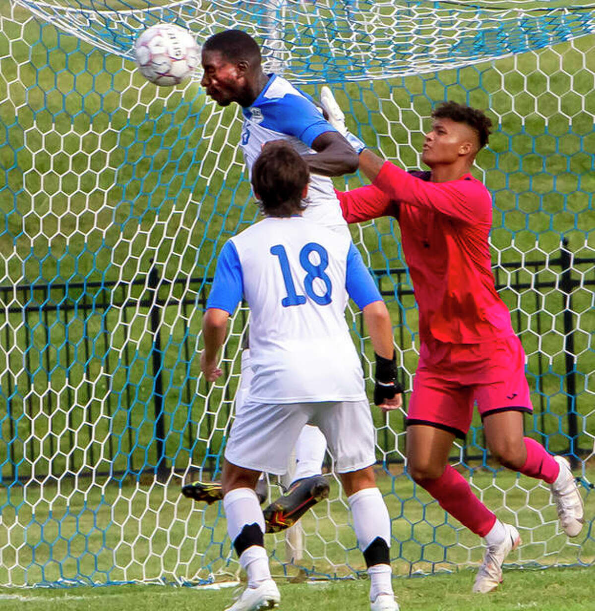 Jovanny Nsonga of LCCC heads the ball away from the Trailblazers' goal as LCCC goalie Eric Walker closes in. Also pictured is LCCC's Morgan Moina (18).