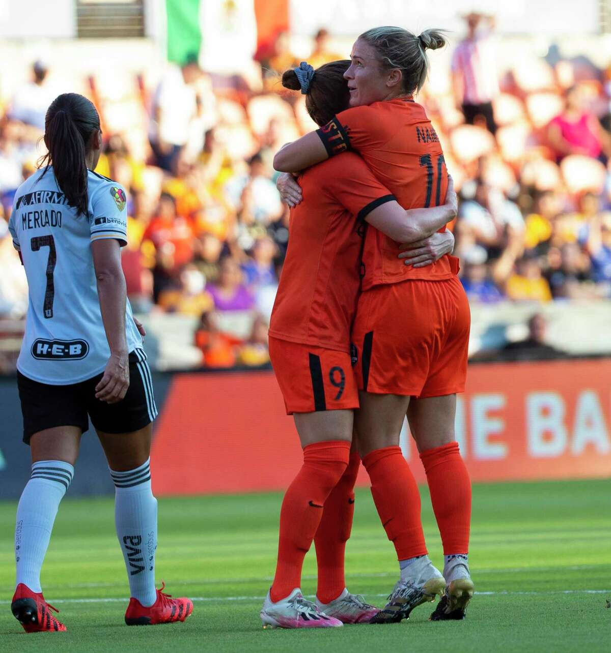 Houston Dash's Christine Nairn (10) and Haley Hanson (9) hug after the Dash scored its first goal during the first half of an international friendly match against Tigres Femenil Sunday, Sept. 19, 2021, at BBVA Stadium in Houston. The goal started with a corner kick from Nairn. Nair is set to retire and join Houston Fire Department Academy.