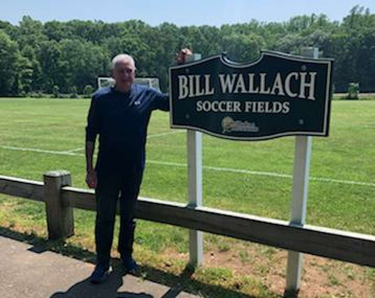 Ex-Guilford soccer coach Bill Wallach stands next to the sign of one field at Cox Elementary School in Guilford that will officially be named after the longtime former coach on Sept. 25, 2021.