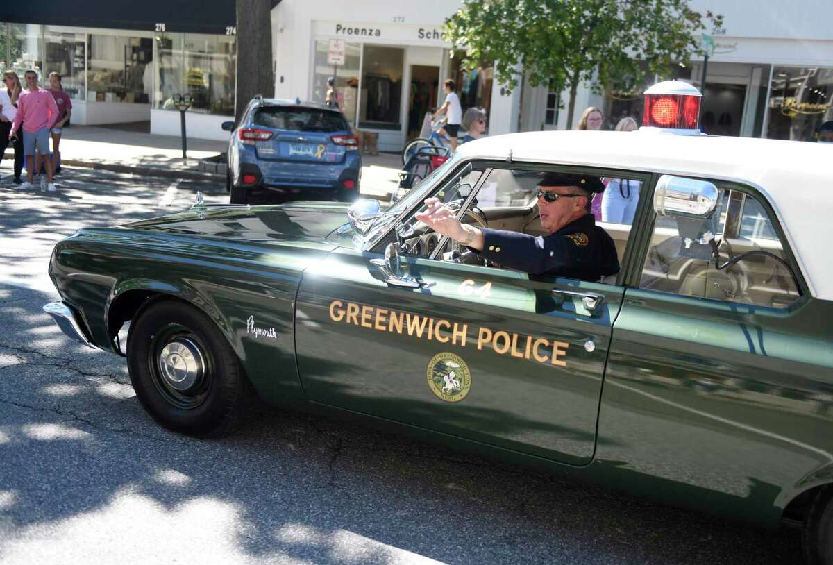 Retired officer and current Greenwich Police dispatcher Mark Wilson drives his 1964 Plymouth police car at the Greenwich Police Department 125th Anniversary Parade in Greenwich, Conn. Sunday, Sept. 19, 2021. The parade was held to celebrate the 125th anniversary of the Greenwich Police Department and honor Greenwich Hospital staff, first-responders, and essential workers who made great sacrifices through the pandemic. After the parade, 10 pipe bands took the stage at Havemeyer Field for a large band performance.