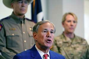 Texas Gov. Greg Abbott, front, speaks in front of Texas National Guard Director Maj. Gen. Tracy Norris, back right, and Director and Colonel of the Texas Department of Public Safety Steven McCraw after Abbott signed a bill providing additional funding for security at the U.S.-Mexico border, Friday, Sept. 17, 2021, in Fort Worth. (AP Photo/LM Otero)