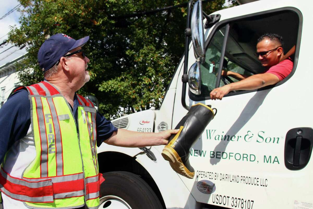 Firefighter John Thompson takes a donation from a driver during the Byram Volunteer Fire Department's biannual boot drive along Delavan Avenue in Byram, Conn., on Saturday September 18, 2021.