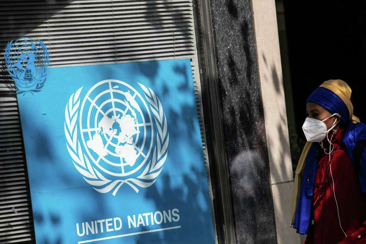 A pedestrian wearing a protective mask passes in front of signage outside the United Nations headquarters in New York on Sept. 22. 2020.