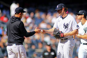 Gerrit Cole (45) of the New York Yankees hands the ball to manager Aaron Boone (17) after being removed in the sixth inning against the Cleveland Indians at Yankee Stadium on September 19, 2021 in New York City.