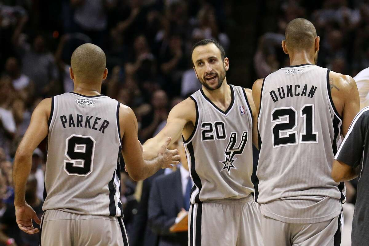 (L-R) Tony Parker #9, Manu Ginobili #20 and Tim Duncan #21 of the San Antonio Spurs celebrate a play as they walk to the bench during a timout in overtime against the Memphis Grizzlies during Game Two of the Western Conference Finals of the 2013 NBA Playoffs at AT&T Center on May 21, 2013 in San Antonio.